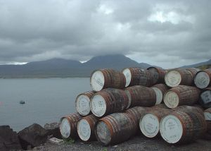 Empty casks outside Bunnahabhain distillery, looking across the Sound of Islay towards the Paps of Jura, shrouded in cloud. Photographed by James Gray, 2001